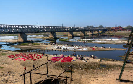 The Indians wash clothes in a dirty river under a bridge and drying clothes on the sand.