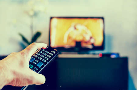 Men with the remote control front of the television. Photo toning in a retro style.