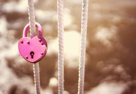 weighs: Pink Wedding closed lock in the form of heart. The castle weighs in at a bridge on a blue sky background. Retro style Stock Photo