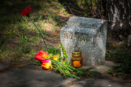 Burning candle and flowers tulips vested at the monument to the Soviet soldier of the red army who died during the second world war. Stock Photo