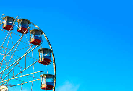 Ferris wheel with a secure closed cabins on background of blue sky