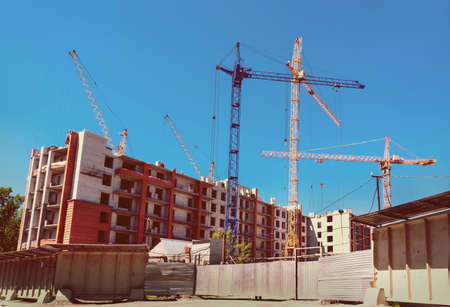 many tall buildings under construction and cranes under a blue sky