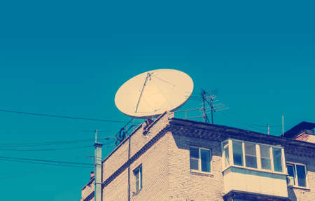 Satellite dish on the roof of a brick building in the background of blue sky. retro vintage filter effect