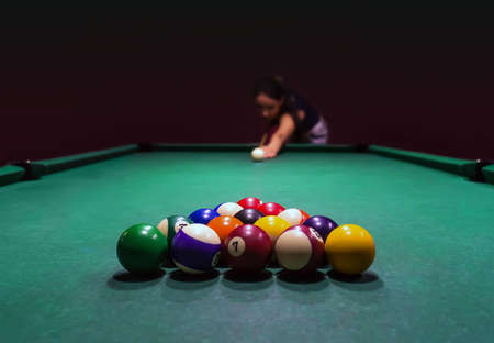 Beautiful girl plays pool in pub and enjoys nightlife