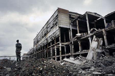 Soldaat in militair uniform staat op de ruïnes van het verwoeste huis. Hete plekken op de planeet. Het concept van de strijd tegen het terrorisme.