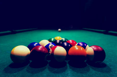 Billards pool game. Color balls in triangle, aiming at cue ball. black night background