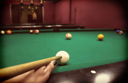 Hand of a Caucasian girl playing billiards pool game. Stock Photo