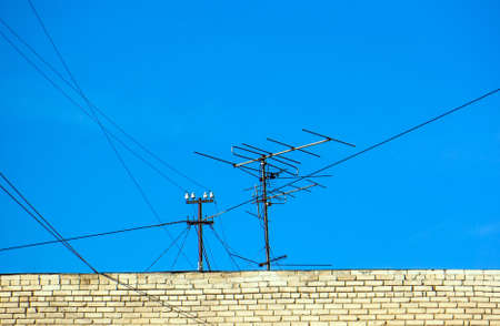Old technology of TV antenna on residence roof.