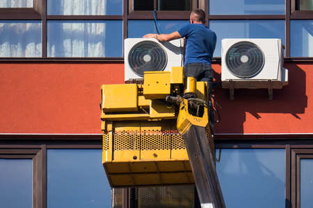 Installation of outdoor air conditioning on a tall building on the crane