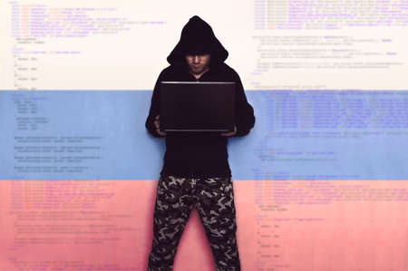 cyber war: A hacker in military uniform with a black hood, with a laptop on the background of Russian flag and the code. Russian computer troops. Information war.