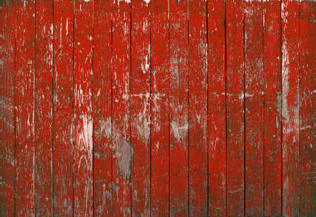 red background wood texture. Vintage old fence with peeling paint red.