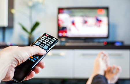 lazybones: Men with the remote control front of the television. A man is relaxing on sofa and watching sports on TV. Stock Photo