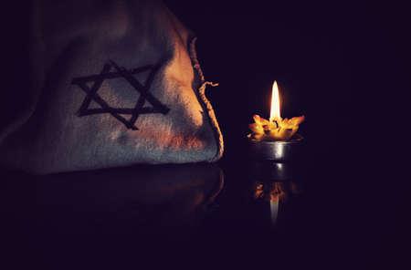 brandende kaars en de ster van david tegen een zwarte achtergrond.