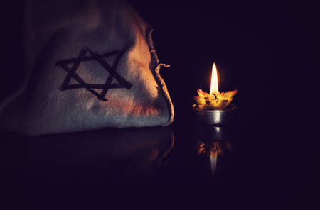 burning candle and the Star of David against a black background. Archivio Fotografico