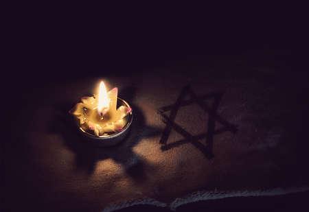 bougie allumée et l'étoile de David sur un fond noir.