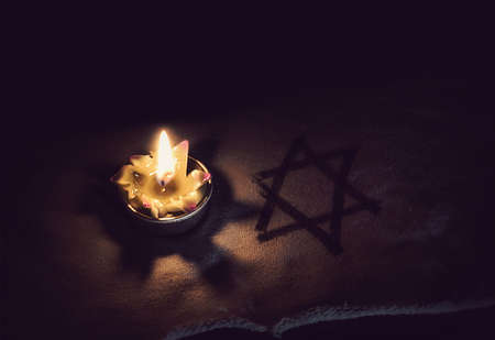 burning candle and the Star of David against a black background. 版權商用圖片