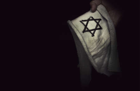 captives: closeup of the Jewish badge star of David in the hand. Stock Photo