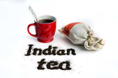 inscription Indian tea on a isolated white background next to the mug and packaging of granular loose black tea