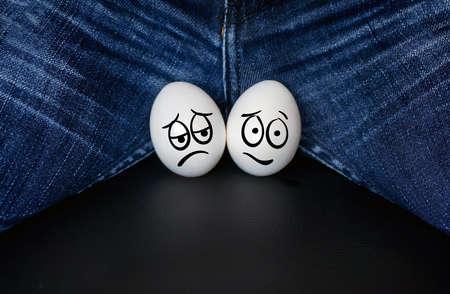 choroby układu moczowo-płciowego u mężczyzn są ilustrowane jako smutne jaja na tle męskiego krocza. wazektomia,