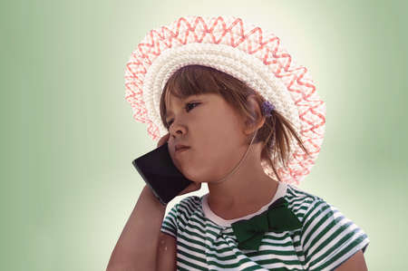puzzlement: Cute little girl speaking on the cell phone. isolated on green background. child with a sad face and a disappointed look