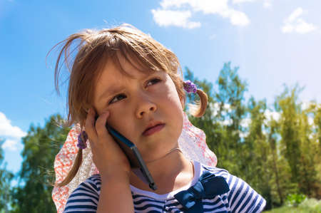 girl child holding a smart phone in hand and talking on the phone with a sad expression in nature
