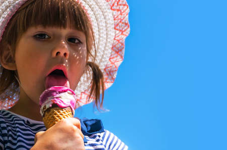 kid with ice cream on blue isolated background. copy space for text