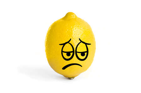 Sour sad face on a lemon.. One lemon isolated on white background. Tropical fruit. Stock Photo