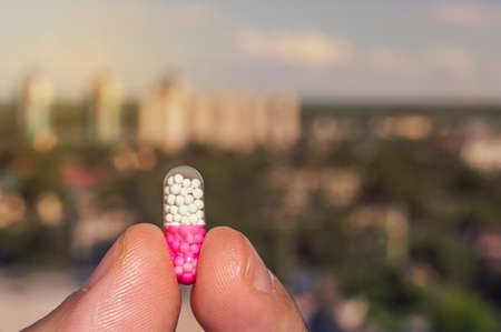sleeping pills: Tablet in the hands of a person on the background of the urban landscape.