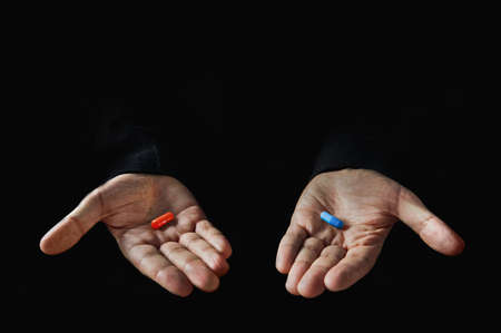Red and blue pills on hand isolated on black background Stockfoto