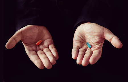 Red tablet in the left palm blue pill in his right hand Foto de archivo