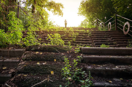 The girl goes up the stairs in an old abandoned Park. The concept of separation or breakup. sky, heaven, death, the soul Stock Photo