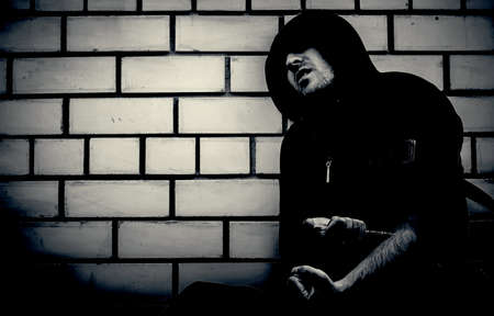 black and white portrait of young sick drug addict man wearing hood holding heroin or cocaine syringe. Boosted contrast to make the darkness of the photo.