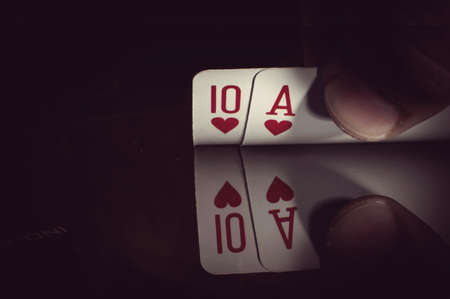 hand holding best classic winning blackjack combination ten and ace hearts Banco de Imagens
