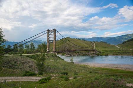 Suspension bridge across mountain river, evening light, blue sky Stock Photo