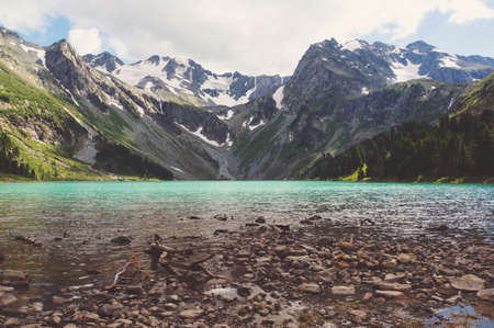 backwater: Rocks near Multinskoe lake, Altai mountains. Russia. The beautiful mountain scenery. The lake in the foreground with mountains in the background on top of which the snow Stock Photo