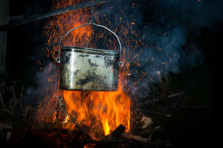 A pot of boiling water on the fire in the forest. Cooking without electricity is a Concept of natural tourist romance away from civilization.