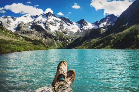 Traveler resting on a mountain plateau. POV view, legs close up on the background of mountain landscape with beautiful turquoise lake