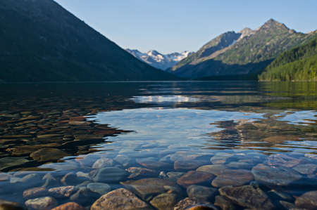 Mountain lakes filled with clean water from melting snow pack fill the wilderness scenery. Multinskoe lake mend the Altai mountains Siberia Russia