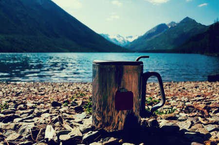 tarde de cafe: Metal thermo mug of water on stones, on blurred background beautiful mountains. The concept of freshness and purity of wild nature.