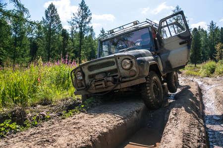 SUV steckte in einer Furche auf einer schlechten unwegsamen Straße in den Wäldern von Sibirien. Russland Standard-Bild - 84211609