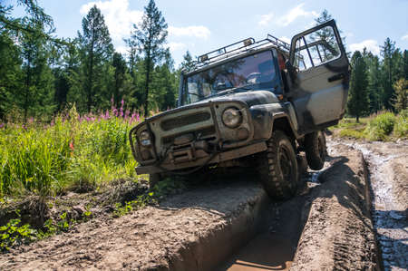 SUV stuck in a rut on a bad impassable road in the woods of Siberia. Russia Zdjęcie Seryjne - 84211609