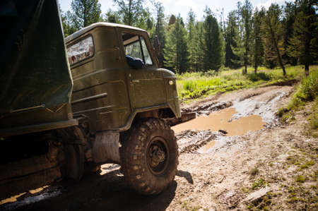 roadless: Heavy powerful truck-terrain vehicle with off-road wheels to overcome obstacles in difficult terrain. Russian military equipment in action. Stock Photo