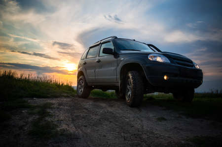 SUV with big wheels at sunset. Russia, Republic of Altai Stock Photo