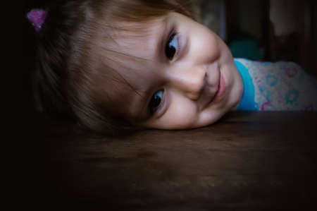 baby lies with his head on the wooden table and staring into space. The girl bowed her head and stares forward with a sly smile