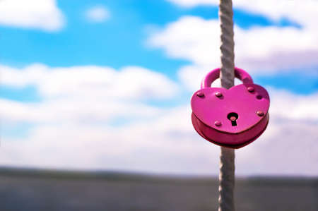 lock symbol: Pink Wedding closed lock in the form of heart. The castle weighs in at a bridge on a blue sky background on a bright Sunny day. Stock Photo
