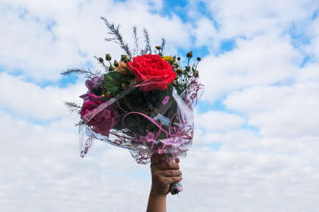 a bouquet of flowers in hand on blue sky background. hand of the child holds a gift a bouquet of beautiful flowers on September 1.