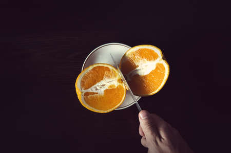sliced orange particles to a steel knife blades on display orange slice, cutting on a wooden table, holding the hand of fruit in the kitchen