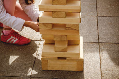 the girl pulls out a wooden block from the tower playing jenga game at street. Play Jung with a very large wooden blocks, outdoor games for children.