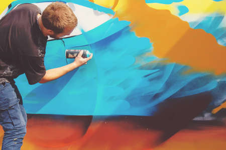 Photo in the process of drawing a graffiti pattern on an old concrete wall. Young long-haired blond guy draws an abstract drawing of different colors. Street art and vandalism concept. Stock Photo