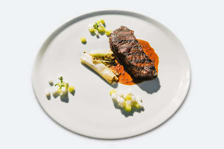 meat table : grilled beef fillet served on white plate isolated over white. Grilled steak with vegetables under the red, white, sweet sour tomato sauce.